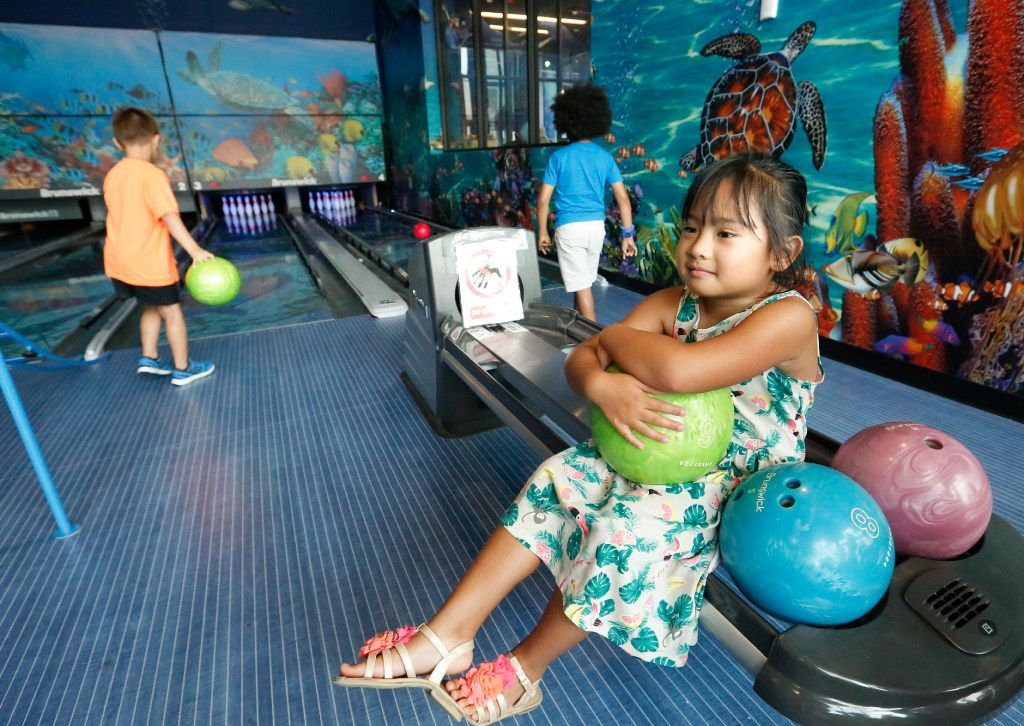 Ellise Bailey patiently waits her turn to bowl at the Children's Learning Adventure bowling alley in McKinney on June 14. The facility has four bowling lanes for the children.