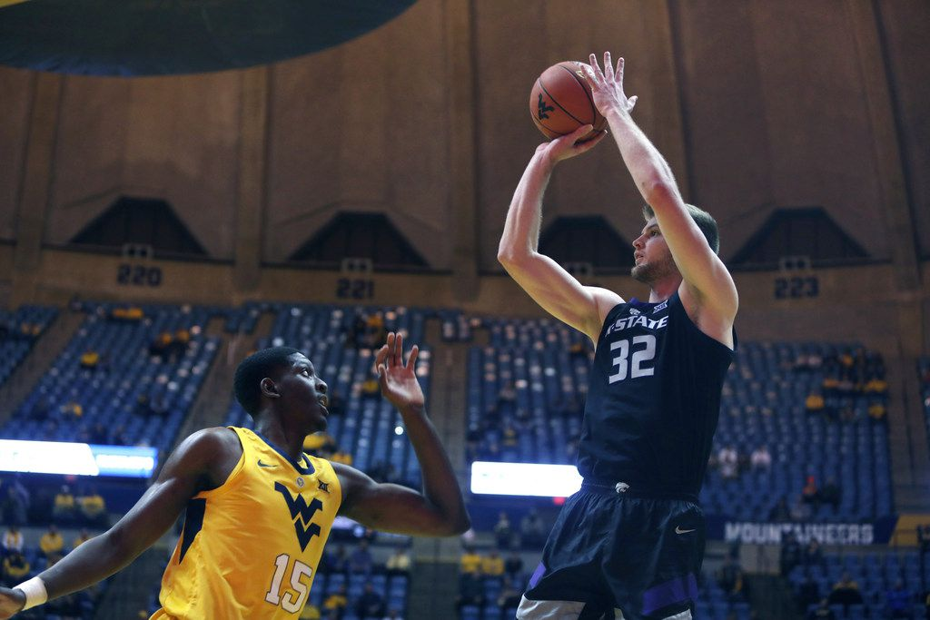 Kansas State forward Dean Wade (32) shoots while defended by West Virginia forward Lamont West (15) during the first half of an NCAA college basketball game Monday, Feb. 18, 2019, in Morgantown, W.Va. (AP Photo/Raymond Thompson)