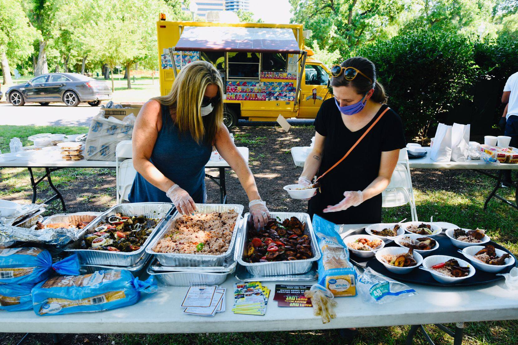 Volunteers Denise Jones (left) and Shoshana McIntosh plate food from One Love Caribbean restaurant during the Potluck Protest to support black-owned restaurants on June 13, 2020 at Reverchon Park in Dallas.
