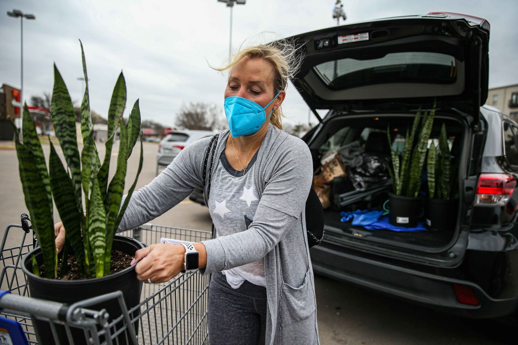 Diana Rodgers, 48, wears a mask as she unloads new plants she bought at Kroger in Dallas into her SUV on Wednesday.