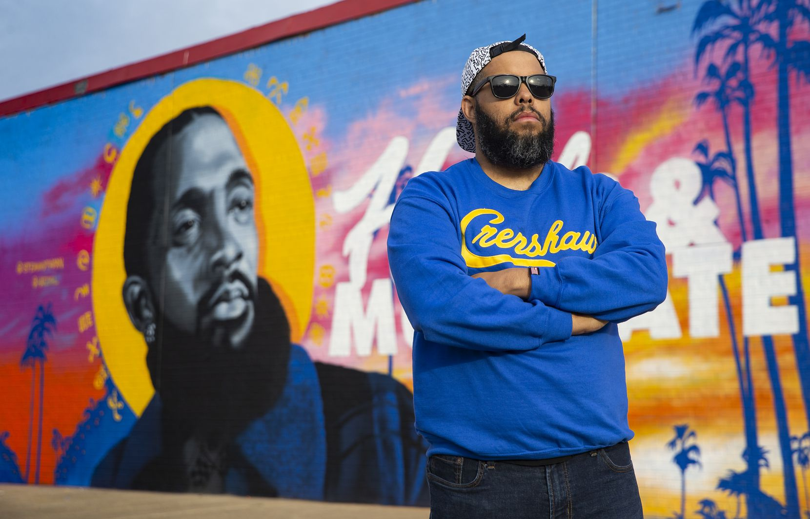 Dallas artist Jeremy Biggers poses in front of his mural dedicated to the late rapper, entrepreneur and community activist Nipsey Hussle at the Glendale Shopping Center on Feb. 22, 2020 in Dallas.