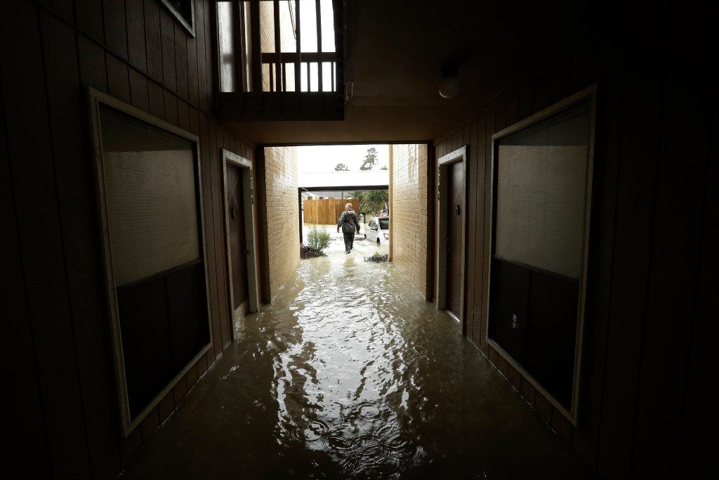 FILE - In this Aug. 29, 2017 file photo, Steven Hathaway searches for people to help in an apartment complex in Kingwood, Texas. Authorities say standing water will contain untreated sewage, along with spilled fuel and toxic waste. They're urging residents to stay out of it when possible. (AP Photo/Gregory Bull, File)