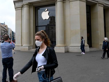 A woman wearing a face mask walks past the closed Apple store in Barcelona on Saturday.