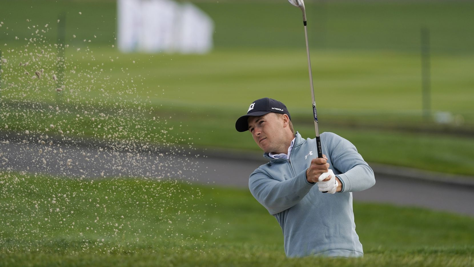 Jordan Spieth follows his shot out of a bunker onto the sixth green of the Pebble Beach Golf Links during the third round of the AT&T Pebble Beach Pro-Am golf tournament Saturday, Feb. 13, 2021, in Pebble Beach, Calif.