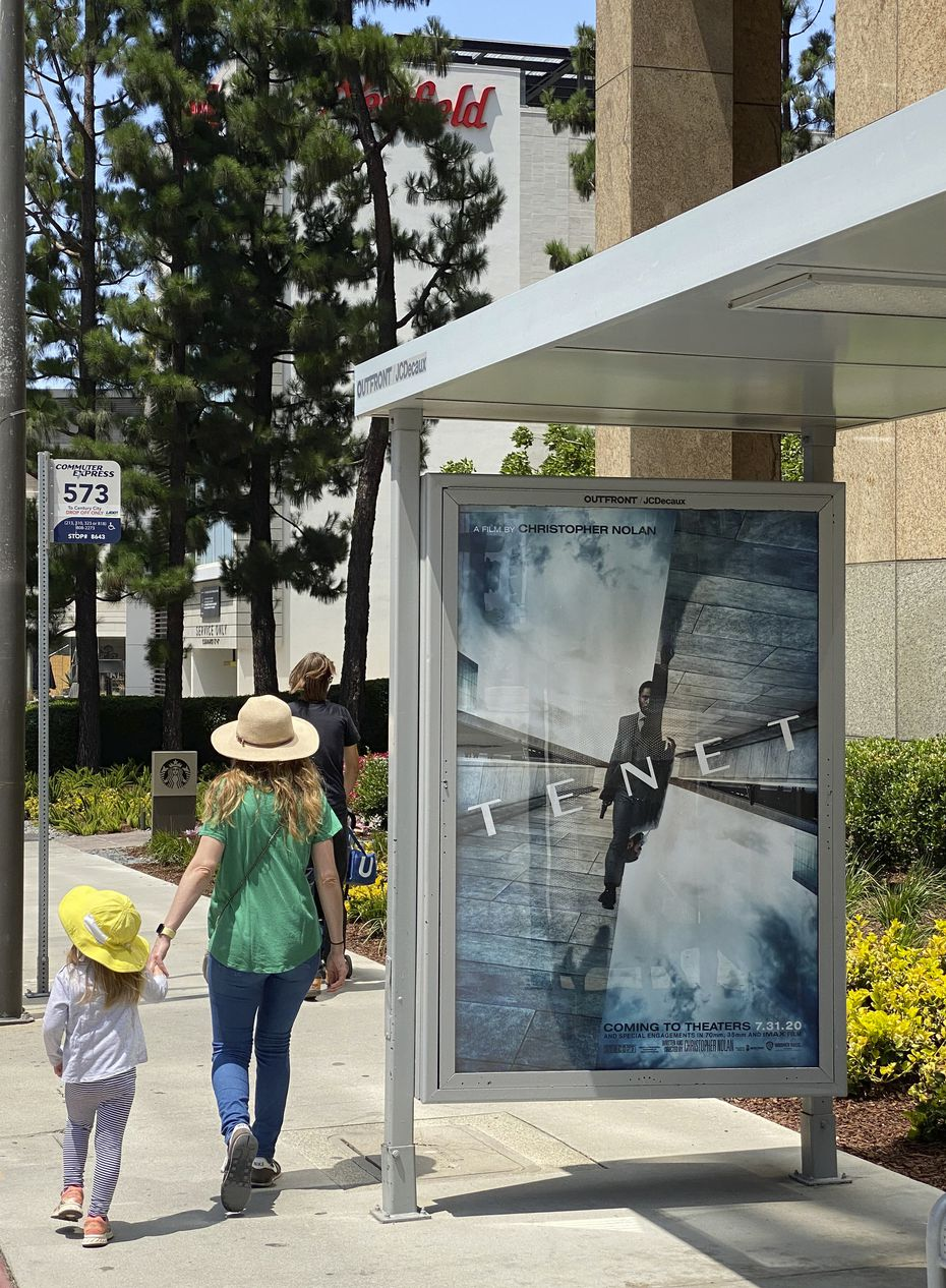 """In this June 27, 2020 photo, people walk by a poster promoting the long-awaited Christopher Nolan film """"Tenet,"""" in Los Angeles. AMC is set to screen the film starting Sept. 3, after several delays."""