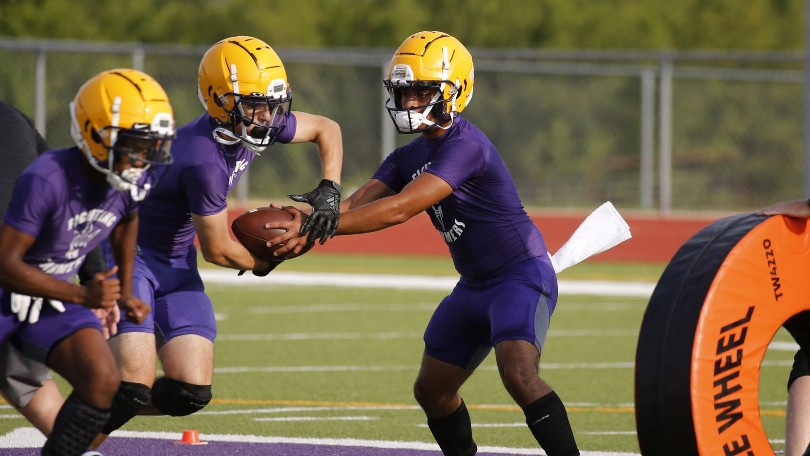 Farmersville quarterback EJ Chairez fakes a handoff to Braden Lair during the first day of high school football practice for the Class 4A schools on Monday, August 3, 2020.