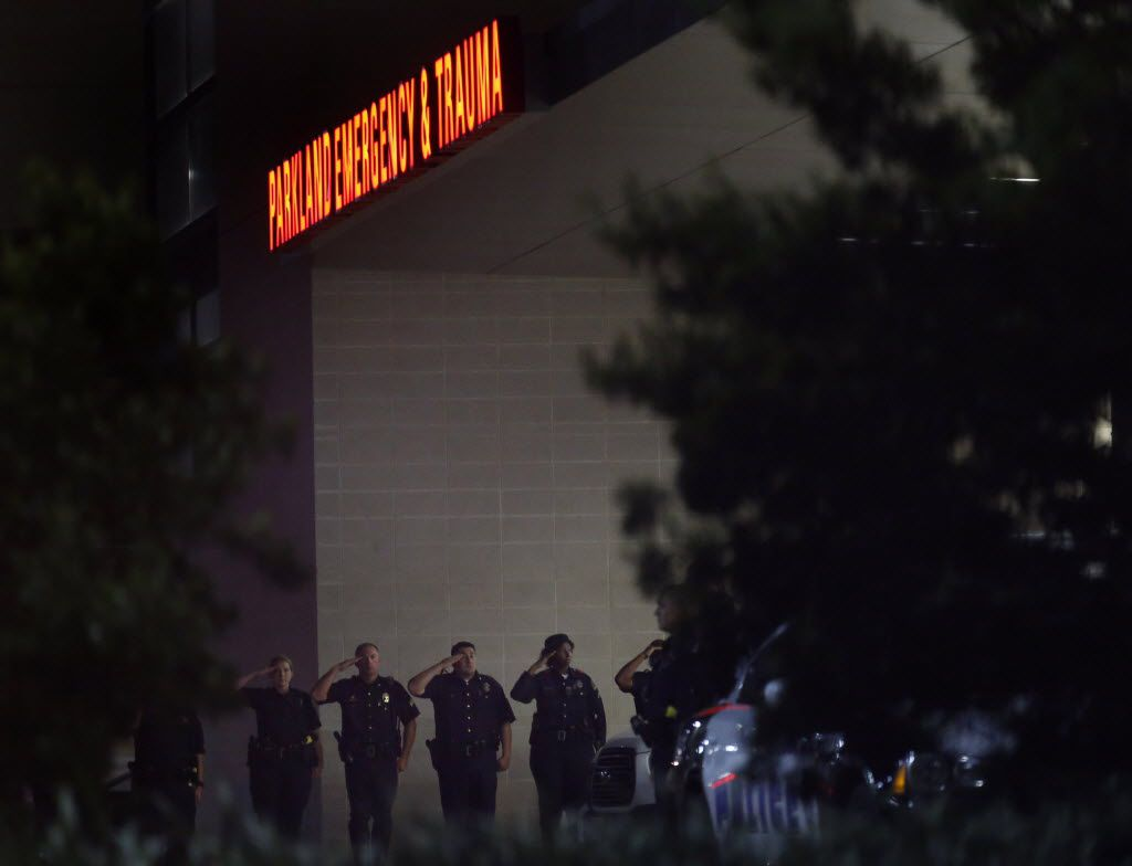 Dallas Police officers stand in salute as fallen officers are transported into UT Southwestern vans, presumably to the Medical Examiner, through a secure entrance at Parkland Hospital in Dallas in the early morning of July 8, 2016 after shots were fired at a Black Lives Matter rally in downtown Dallas on Thursday, July 7, 2016. Dallas protestors rallied in the aftermath of the killing of Alton Sterling by police officers in Baton Rouge, La. and Philando Castile, who was killed by police less than 48 hours later in Minnesota. (Rose Baca/The Dallas Morning News)