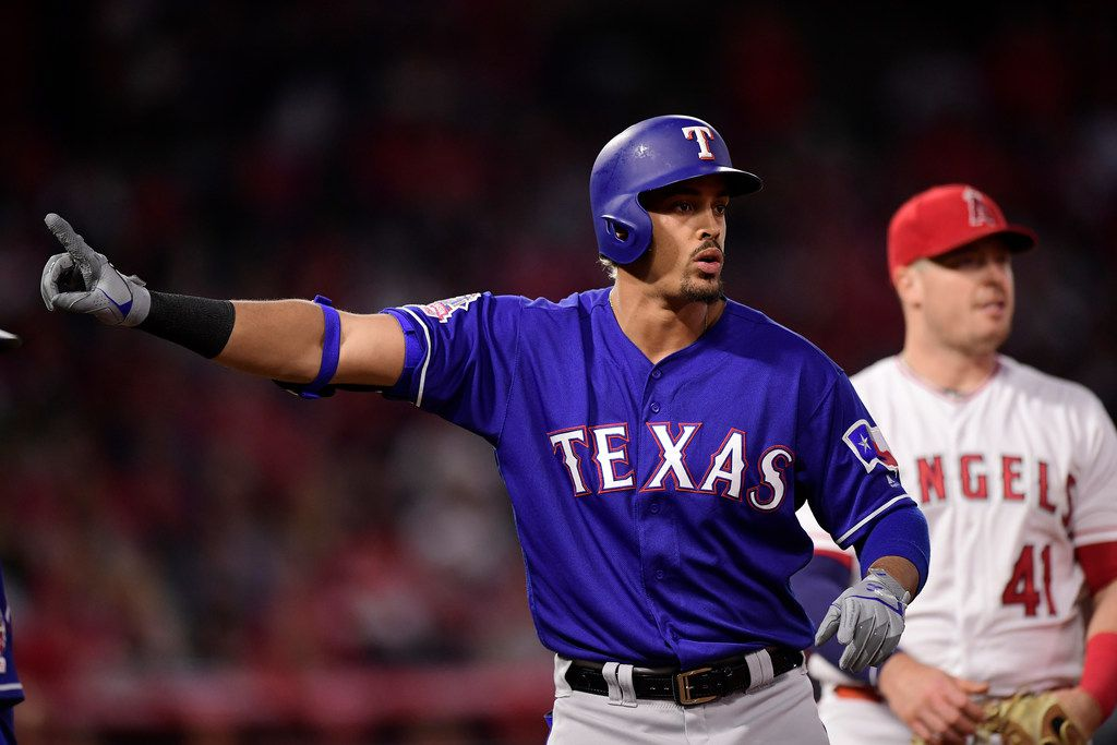 Texas Rangers' Ronald Guzman, left, gestures as he waits, along with Los Angeles Angels first baseman Justin Bour, for a ruling on his apparent two-run home run during the first inning of a baseball game Thursday, April 4, 2019, in Anaheim, Calif. The home run was confirmed after review. (AP Photo/Mark J. Terrill)