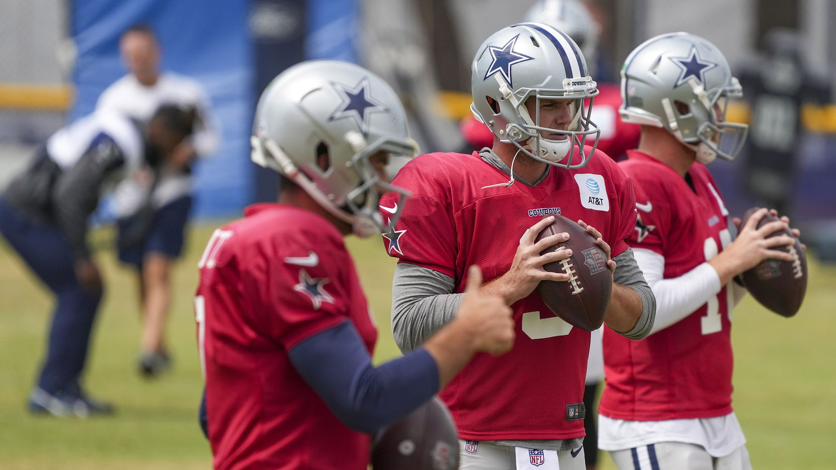 Dallas Cowboys quarterback Garrett Gilbert (3) runs a drill with Ben DiNucci (7) and Cooper Rush (10) during a practice at training camp on Wednesday, Aug. 11, 2021, in Oxnard, Calif.