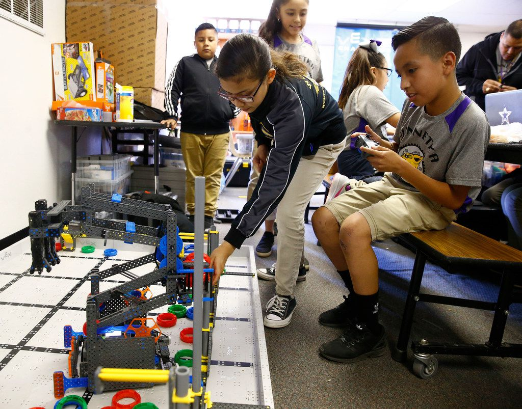 Joshua Salazar (right with remote) and Cassandra Gayton use robots to pick up points as they practice at Winnetka Elementary for the Vex Robotics World Championship.