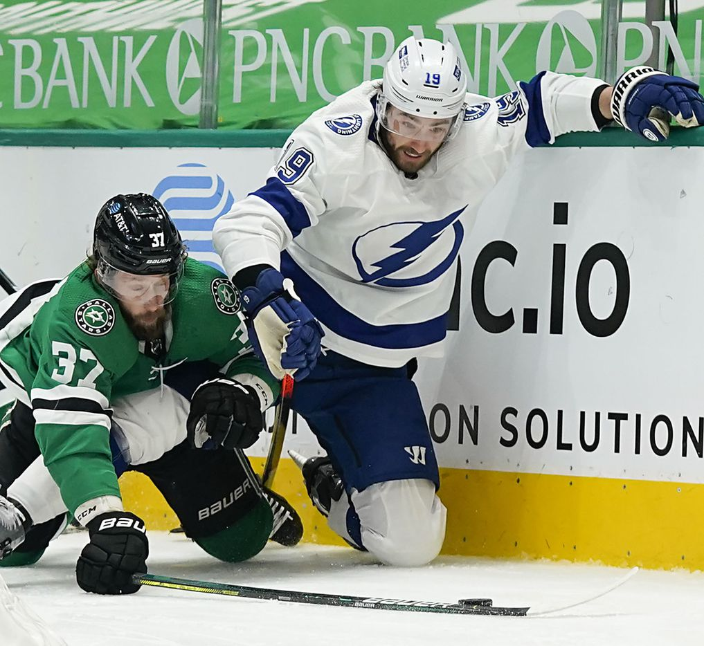Dallas Stars center Justin Dowling (37) fights for the puck against the boards with Tampa Bay Lightning right wing Barclay Goodrow (19) as they hit the ice during the second period of an NHL hockey game at the American Airlines Center on Thursday, March 25, 2021, in Dallas. (Smiley N. Pool/The Dallas Morning News)