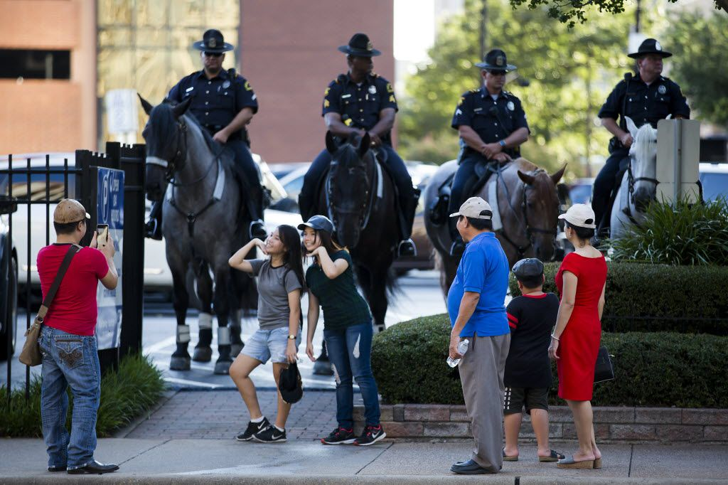 Bystanders pose for photos with mounted police across the street from a rally in downtown Dallas on Thursday, July 7, 2016. Dallas protestors rallied in the aftermath of the killing of Alton Sterling by police officers in Baton Rouge, Louisiana and Philando Castile, who was killed by police less than 48 hours in Minnesota. (Smiley N. Pool/The Dallas Morning News)