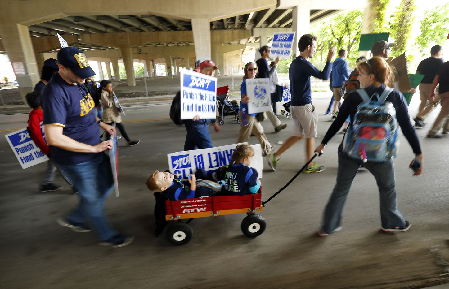 The Steib family of Sachse, Texas (from left) Clovis, Jake, Sara and Sona joined thousands of other March For Science supporters as they march under Interstate 30 on their way to Fair Park's Earth Day celebration, Saturday, April 22, 2017. (Tom Fox/The Dallas Morning News)