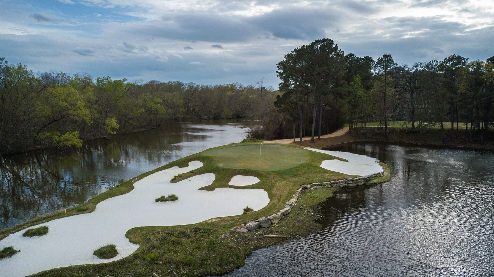An aerial view of No. 15 at Whispering Pines Golf Club in Trinity, Texas, is a 179-yard par-3 hole from the Spirit tees.  It is annually voted one of the most beautiful holes in Texas by Texas Golf panelists. Caney Creek, which feeds Lake Livingston, is on the left.