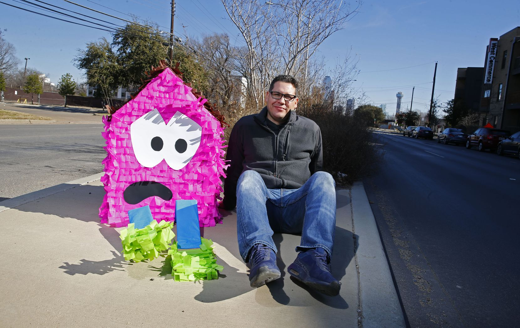 "Dallas artist Giovanni Valderas with one of his ""sad house"" piñatas in 2018. He displays his works in public to protest the lack of affordable housing in Oak Cliff."