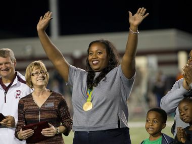 Michelle Denee Carter (center), Rio Olympics gold medalist shot putter waves to the crowd while being honored at halftime during the high school football game between Lake Ridge High School and Red Oak High School at Texas Football Stadium on Oct. 7, 2016 in Red Oak, Texas.