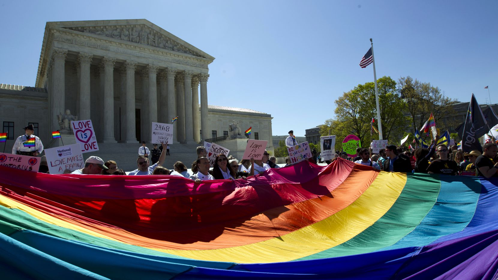 In this April 28, 2015 file photo, demonstrators stand in front of a rainbow flag of the Supreme Court in Washington, as the court was set to hear historic arguments in cases that made same-sex marriage the law of the land. Two Texas judges say their religious beliefs allow them to decline to officiate at same-sex marriages.