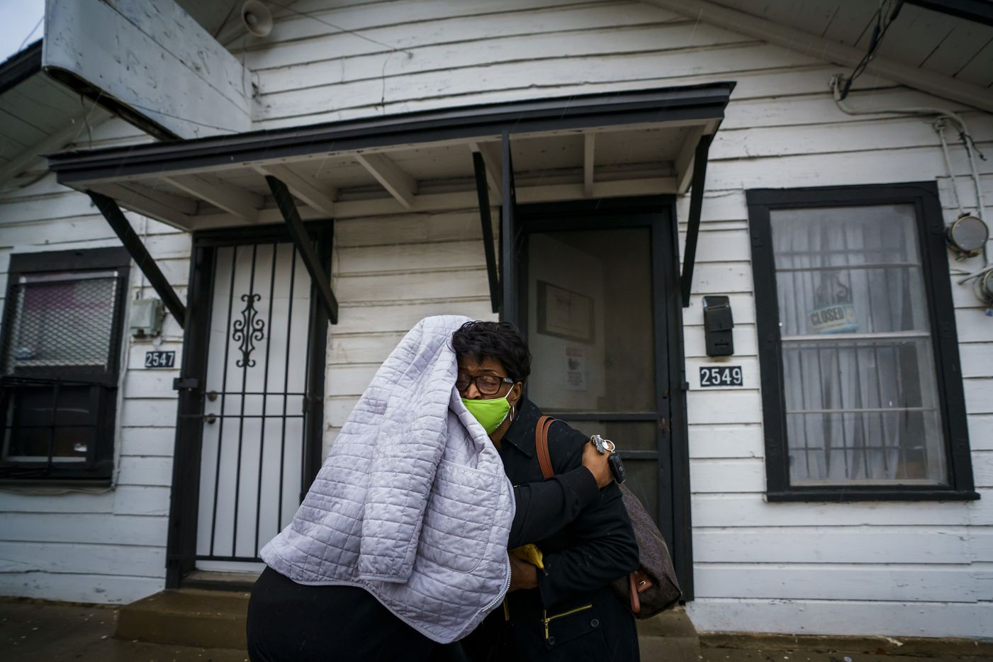 Earnestine Tarrant gets a hug from client Altha Hearne, who wears her jacket over her head to protect her hair from the rain, after Hearne was Tarrant's final client at her hair salon in South Dallas.