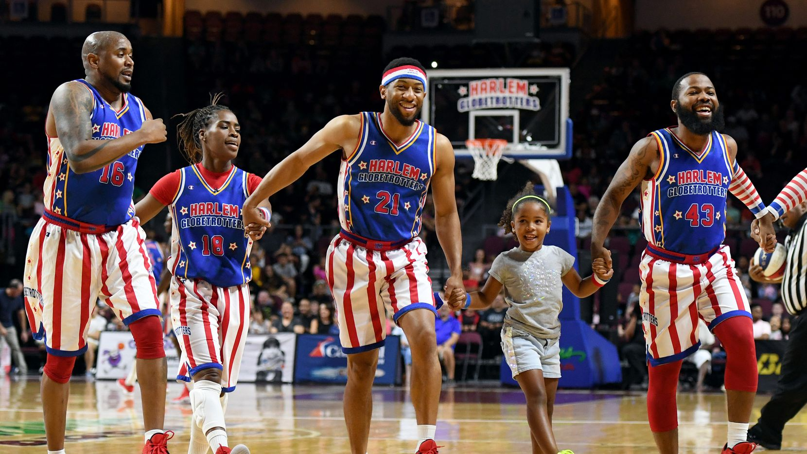 Gianna Burney, 6, skips with Harlem Globetrotters players during a team appearance in Las Vegas.