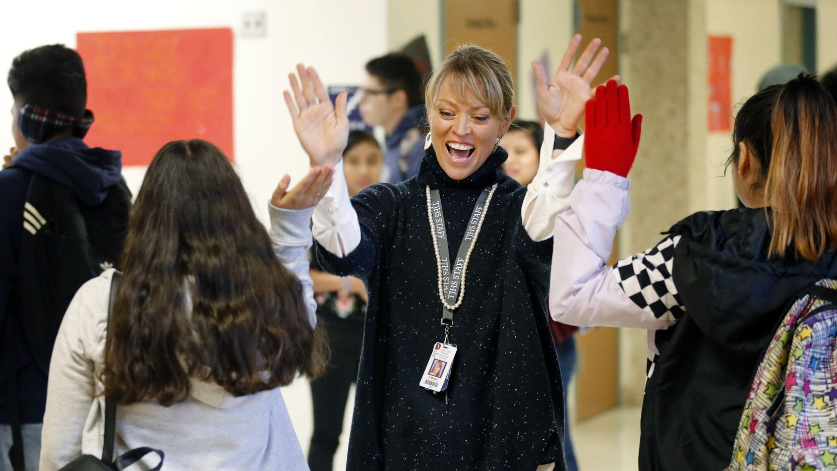 Thomas Jefferson High School principal Sandi Massey greeted her students with high-fives as they arrive at their new school, Thomas A. Edison Middle Learning Center in West Dallas, last October.
