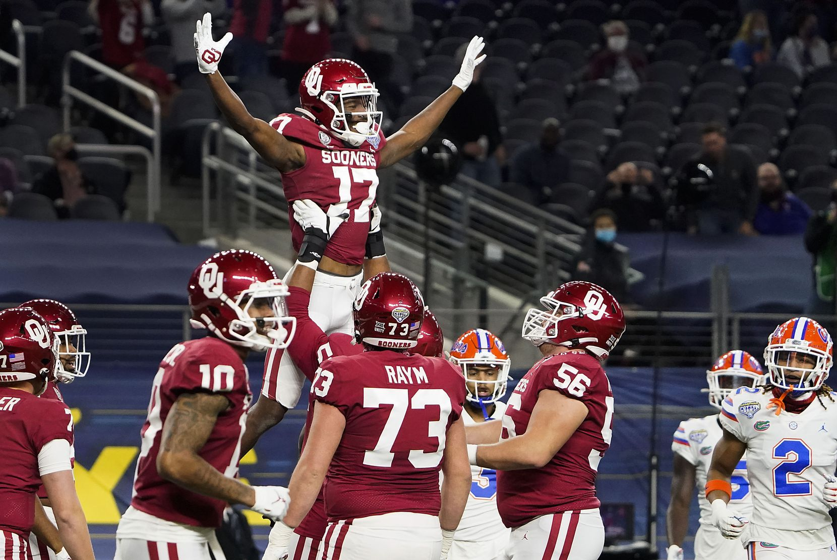 Oklahoma wide receiver Marvin Mims (17) celebrates with offensive lineman Tyrese Robinson (52) after catching a 27-yard touchdown pass during the first half of the Cotton Bowl Classic against Florida at AT&T Stadium on Wednesday, Dec. 30, 2020, in Arlington. (Smiley N. Pool/The Dallas Morning News)