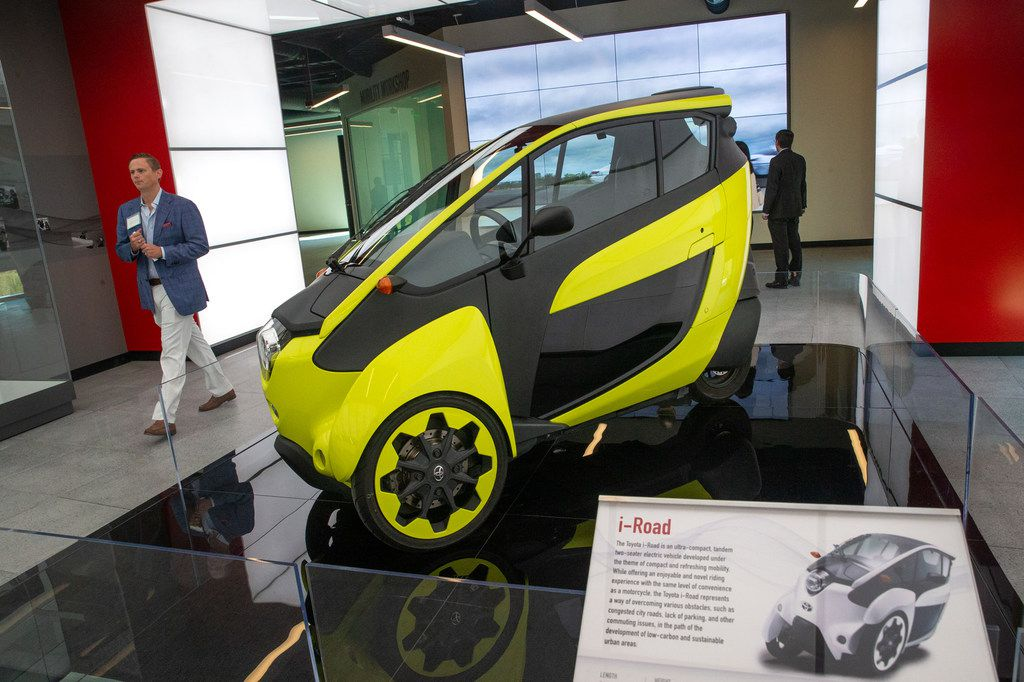 Robert Paulsen walks past a display of a Toyota i-Road ultracompact two-seater electric vehicle during the grand opening of the Toyota Experience Center at the Toyota North American headquarters in Plano, Texas, on Wednesday, Aug. 7, 2019. The center is the motor company's first and only comprehensive museum space. (Lynda M. Gonzalez/The Dallas Morning News)
