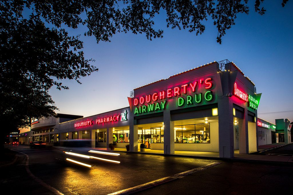 Neon lights up the flagship Dougherty's Pharmacy in Preston Royal Village as night falls.