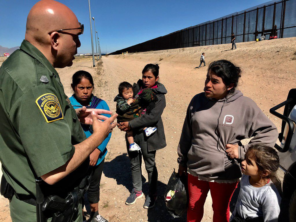 Migrants crossed the border and turned themselves in to the border patrol along a border fence in an area known as El Paso's Lower Valley in the Ysleta area. Border Patrol Agent Joe Romero talks to women from Guatemala on March 6, 2019, who are saying their children are hungry and tired.