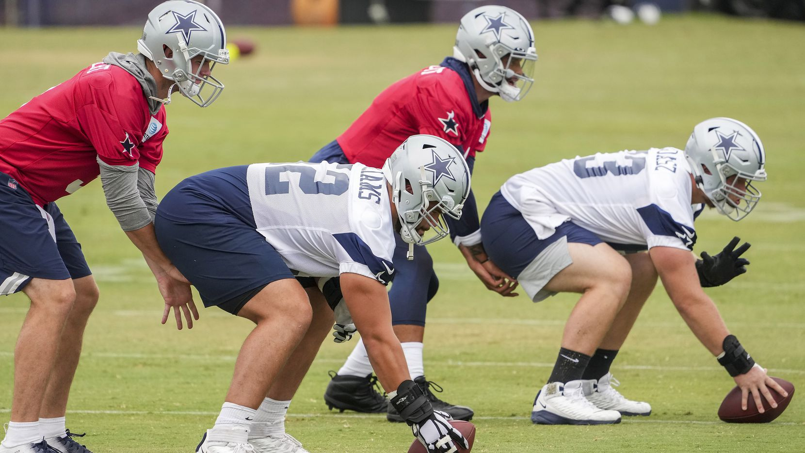 Dallas Cowboys guard Connor Williams (52) works at center with Tyler Biadasz (63) and quarterbacks Garrett Gilbert (left) and Dak Prescott during a practice at training camp on Sunday, July 25, 2021, in Oxnard, Calif.