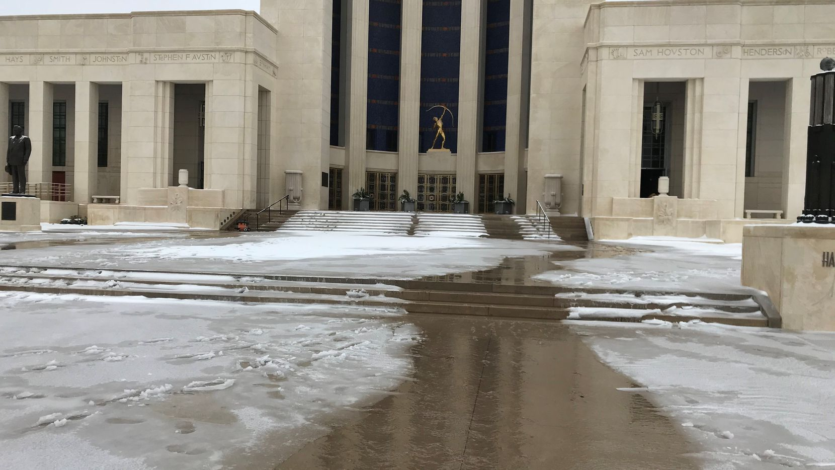 Water flows from the entrance at the Hall of State in Dallas on Feb. 17, 2021. The building was one of several Fair Park facilities that sustained water damage from broken water pipes during the winter storm.