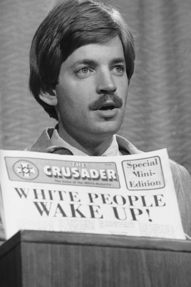 David Duke, Grand Imperial Wizard of the Ku Klux Klan, talks to reporters in Denver on Oct. 13, 1977 as he announced that the KKK is filing a friend of the court brief in a Supreme Court case involving affirmative action in higher education. In the foreground is a Klan newspaper that Duke propped against his microphone.