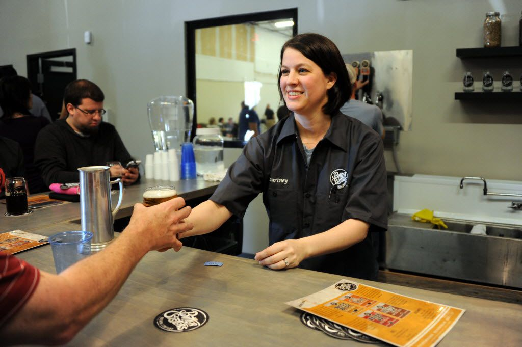 Bartender Courtney Ehinger hands a guest beer at the opening of Bitter Sisters Brewing Company in Addison, TX on March 28, 2015.