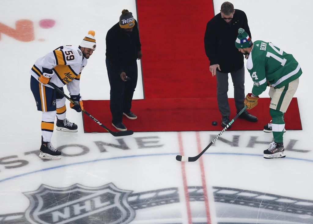 Ricky Williams, second from left, and Troy Aikman, third from left, drop pucks for Nashville Predators defenseman Roman Josi (59) and Dallas Stars left wing Jamie Benn (14) prior to a NHL Winter Classic matchup between the Dallas Stars and the Nashville Predators on Wednesday, January 1, 2020 at Cotton Bowl Stadium in Dallas. (Ryan Michalesko/The Dallas Morning News)