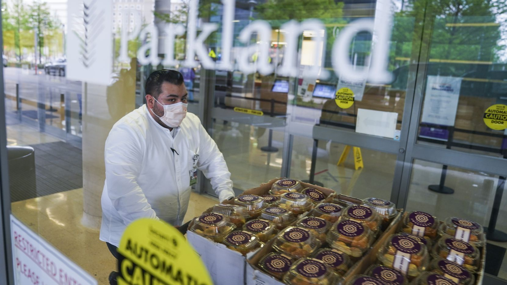 Guest services representative Nahum Hernandez rolls a cart full of desserts from Bigdash Ice Cream & Pastries through the main entrance of Parkland Hospital on Friday, April 17, 2020 in Dallas. Restaurants dropped off over 1,000 meals and 1,500 desserts for doctors, nurses and staff  The effort was organized by local Muslim business leaders. (Ashley Landis/The Dallas Morning News)