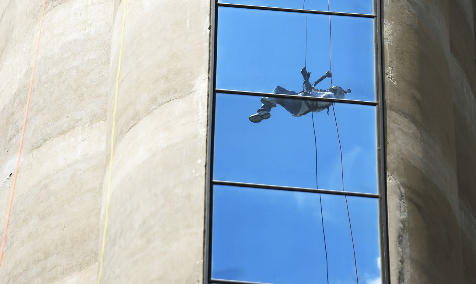 """David Rogers is reflected in a glass panel on Reunion Tower as he rappels off of Reunion Tower during the Shatterproof Challenge Rappel Dallas event on May 13. The event raised money for Shatterproof, a nonprofit founded by Rogers in memory of his son, Brandon """"Bubba"""" Rogers, who died as a result of heroin addiction."""