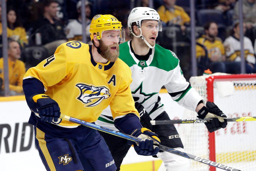 Nashville Predators defenseman Mattias Ekholm (14), of Sweden, and Dallas Stars defenseman Jamie Oleksiak battle in the second period of an NHL hockey game Thursday, March 5, 2020, in Nashville, Tenn.