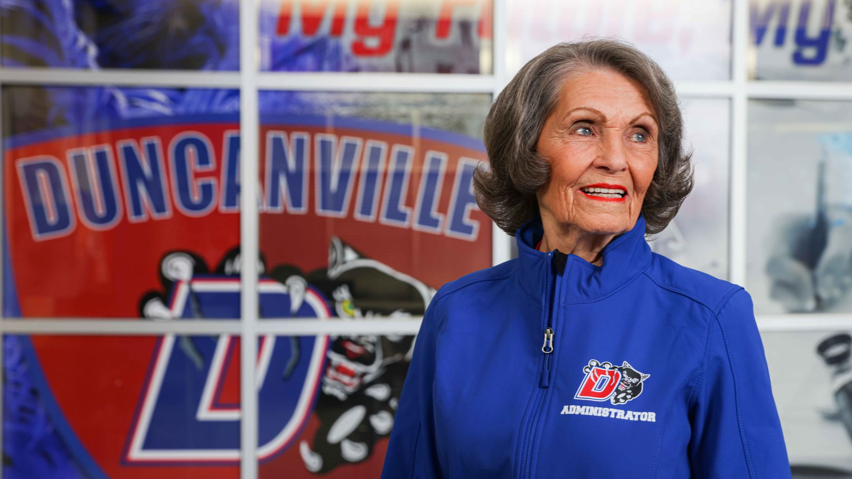 Flo Judd poses in the main hall of the school in Duncanville on Jan. 29, 2021. Judd, 81-year-old associate principal at Duncanville High School, is in her 50th year in education. Like nearly all K-12 educators in Texas, she's working on campus every day, but she hasn't been able to find a coronavirus vaccine, despite signing up with multiple counties around the Dallas area.