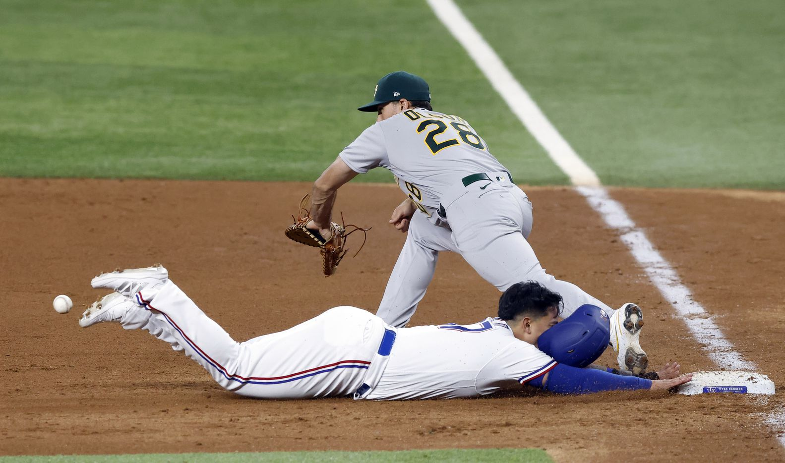 Texas Rangers Yohel Pozo (37) races back to first on a fly out to left field as Oakland Athletics first baseman Matt Olson (28) has trouble fielding the ball in the sixth inning at Globe Life Field in Arlington, Saturday, August 14, 2021.(Tom Fox/The Dallas Morning News)