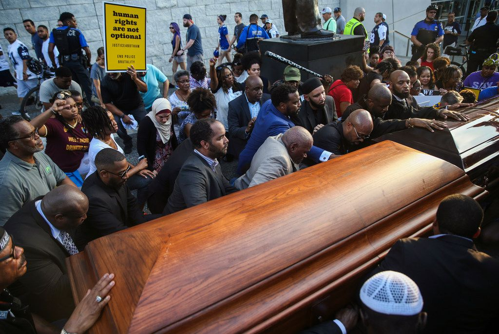 Members of the clergy and community kneeled  around two empty coffins  during a protest prior to the start of the Dallas Cowboys' game against the New York Giants on Sunday.