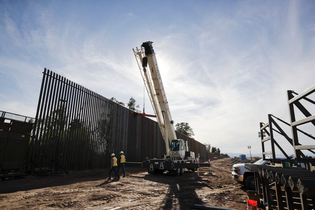 """In this March 5, 2018, photo, construction continues on a new, taller version of the border structure in Calexico, Calif. President Donald Trump threatened to veto the $1.3 trillion spending bill, which passed by the House on March 22, because his proposed border wall with Mexico was not """"fully funded."""""""