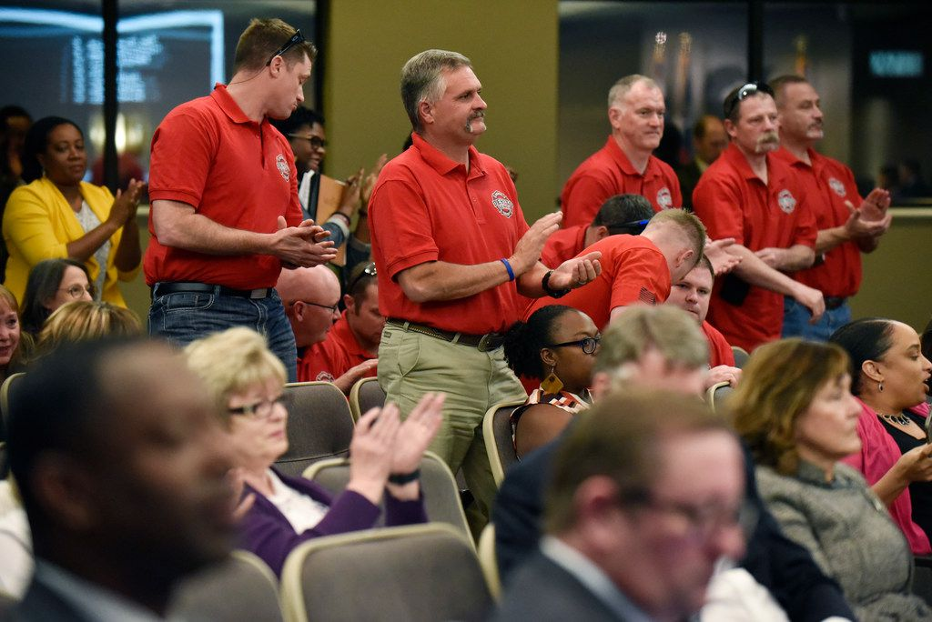 DeSoto Firefighter Craig Kirk, center, stands with other fire fighters as they applaud the vote of DeSoto city council for creating a paid parental leave program for city employees in DeSoto during a city council meeting, Tuesday April 02, 2019 at the Jim Baugh Government Center in DeSoto. The council voted in favor of creating the program to pay city employees for parental leave. Ben Torres/Special Contributor