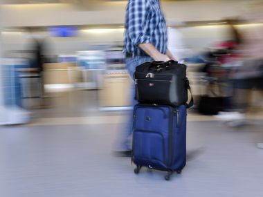 An American Airlines passengers rolls his luggage to check-in in Terminal A at Dallas-Fort Worth International Airport, Wednesday, March 24, 2021. (Tom Fox/The Dallas Morning News)