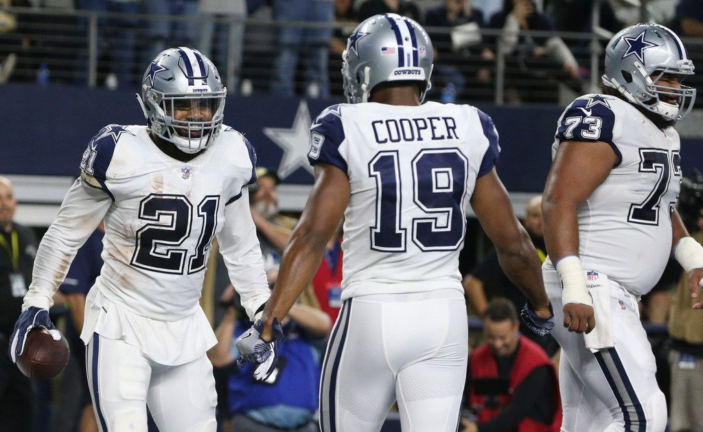 Dallas Cowboys running back Ezekiel Elliott (21) and wide receiver Amari Cooper (19) celebrate a touchdown during the first half of a matchup between the Dallas Cowboys and the New Orleans Saints on Thursday, Nov. 29, 2018 at AT&T Stadium in Arlington, Texas. (Ryan Michalesko/The Dallas Morning News)
