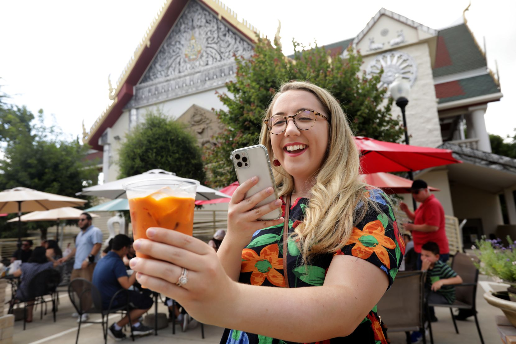 Julie Wells takes a photo of her Thai tea during the Sunday Thai Food Market.