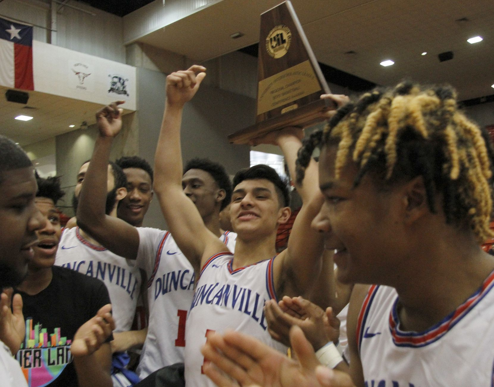 Duncanville guard Cedric Baty (1) raises the Class 6A Region 1 championship trophy as he celebrates with teammates following the Panthers' 59-43 victory over Odessa Permian to gain a berth in the UIL state tournament. The two teams played in the Class 6A Region 1 championship boys basketball playoff game at Wilkerson-Greines Activity Center in Fort Worth on March 7, 2020.