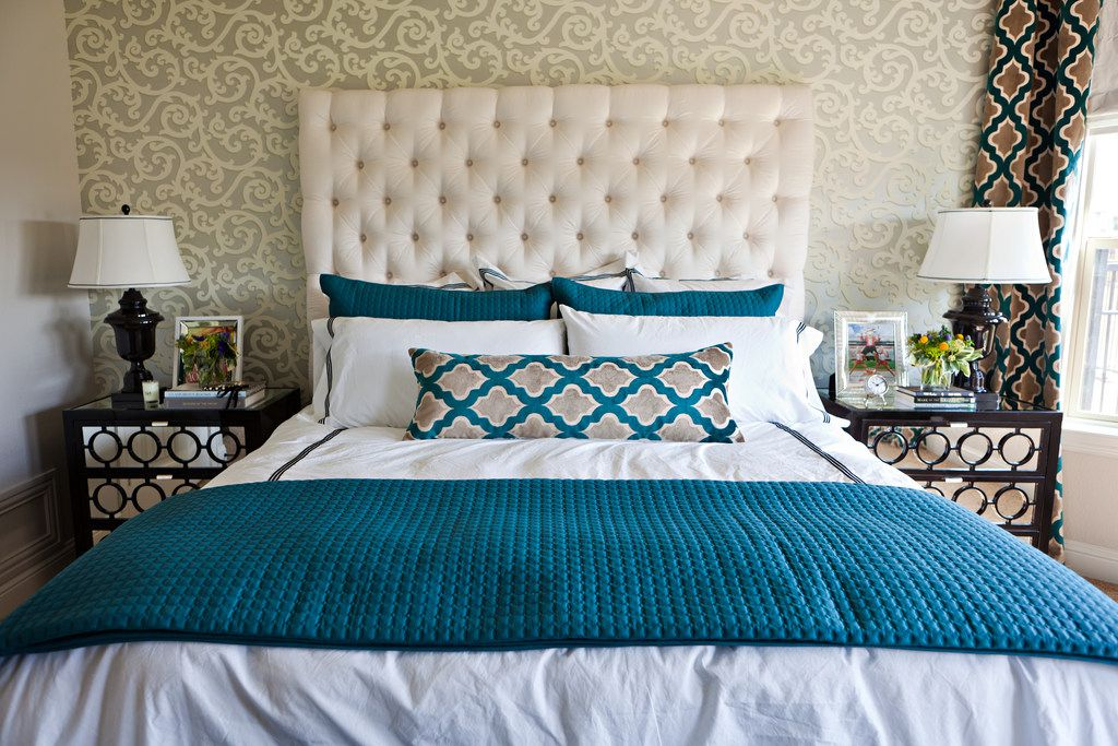When going with bold patterns in other areas of the room, simple, classic options on the bed keep things from getting too crazy, says Abbe Fenimore.