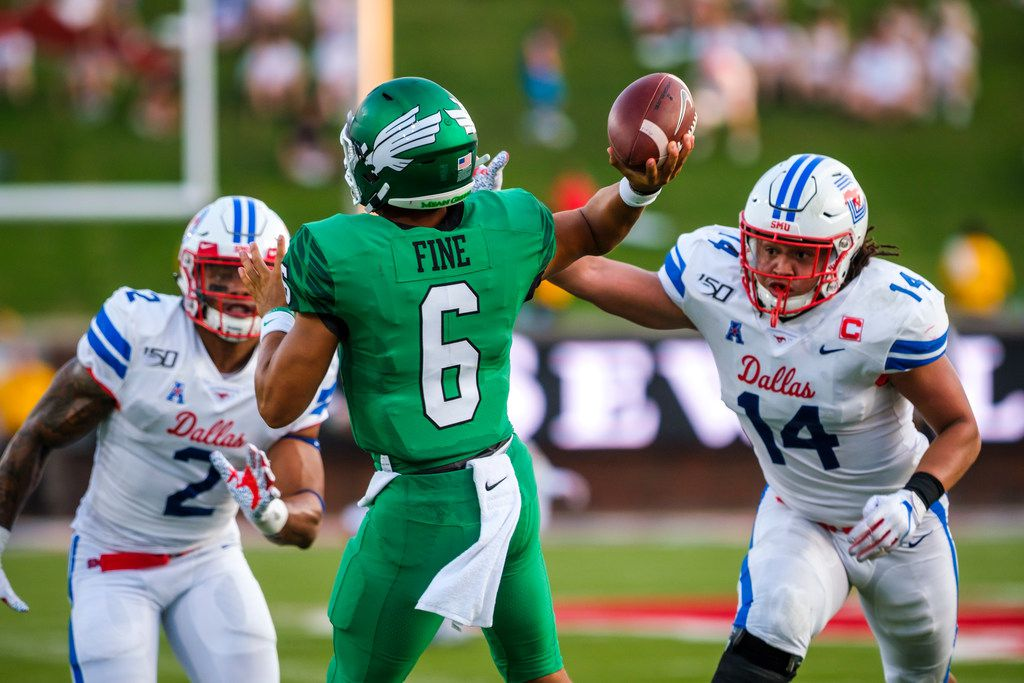FILE — UNT quarterback Mason Fine (6) throws a pass under pressure from SMU linebacker Richard Moore (14) and safety Patrick Nelson (2) during the first half of an NCAA football game at Ford Stadium on Saturday, Sept. 7, 2019, in Dallas.