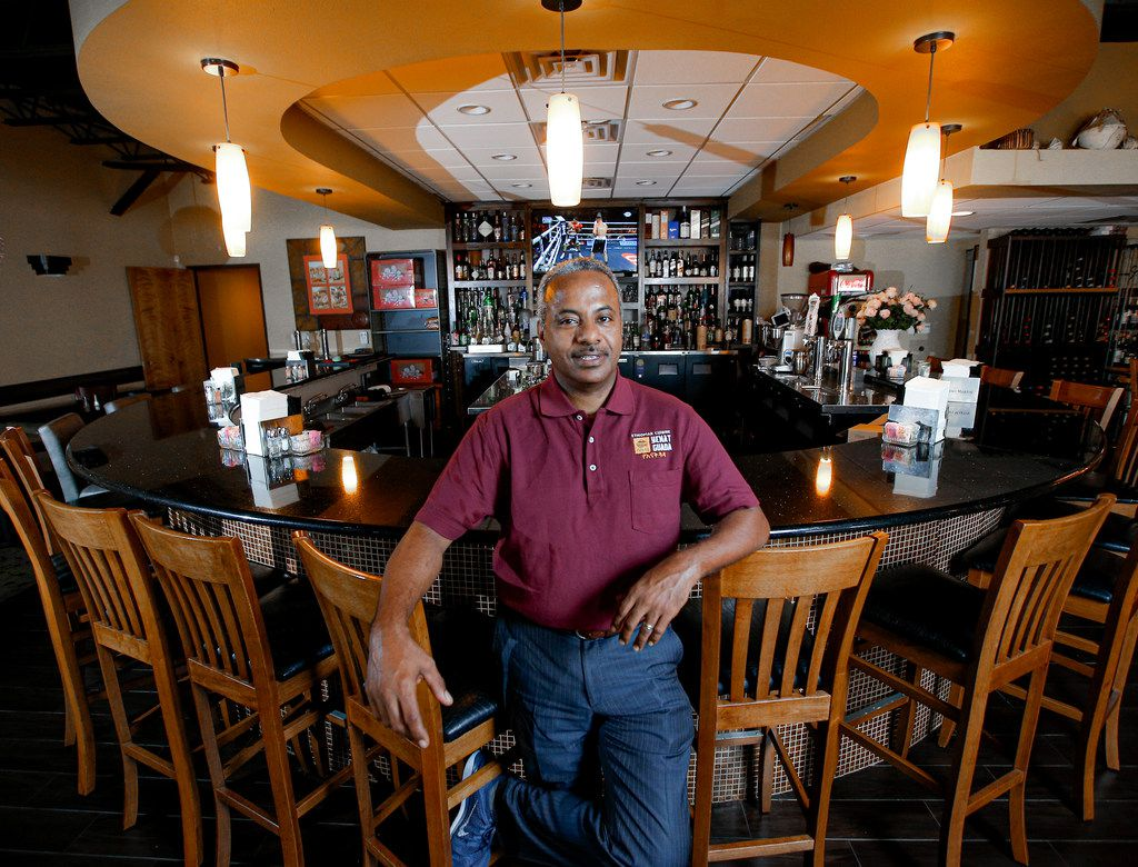 Kassahun Kebede, an immigrant from Ethiopia, stands in his restaurant, Yenat Guada Ethiopian Cuisine, on Aug. 9, 2019.