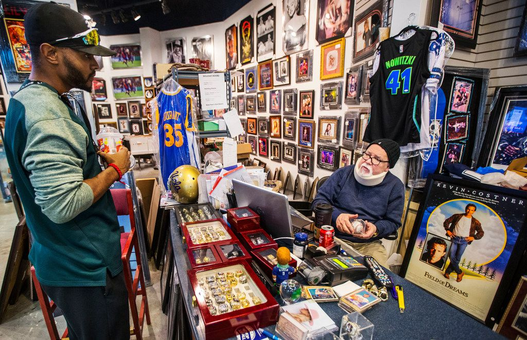 Kevin Junior (left) listens to owner Sheldon Rudman as he tries to sell a signed baseball to Rudman at Collector's Heaven at Music City Mall in Lewisville.