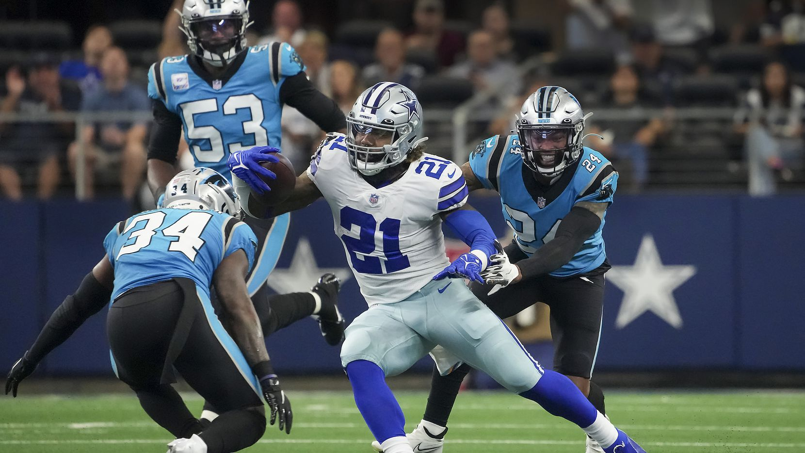 Dallas Cowboys running back Ezekiel Elliott (21) finds a seem between Carolina Panthers defensive back Sean Chandler (34), cornerback A.J. Bouye (24) and defensive end Brian Burns (53) to pick up a first down during the first half of an NFL football game at AT&T Stadium on Sunday, Oct. 3, 2021, in Arlington.